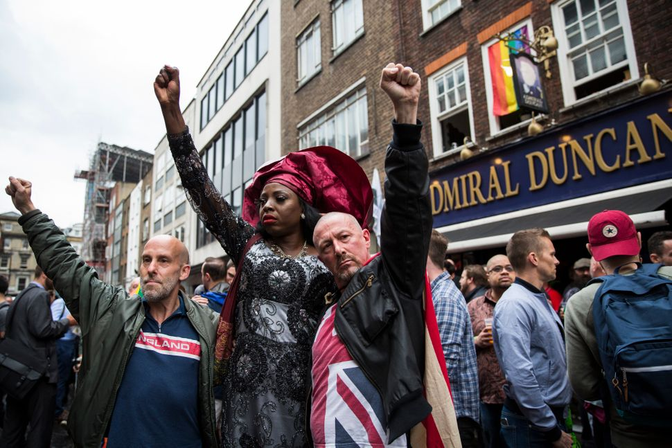 People hold their fists in the air during a vigil for the victims of the Orlando nightclub shooting outside the Admiral Dunca