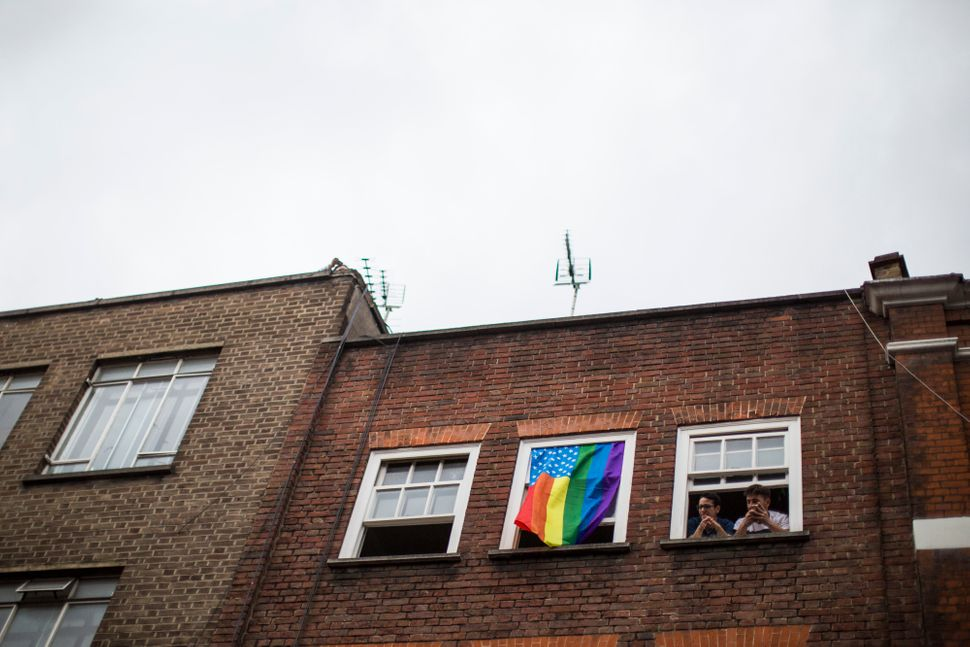 People look out of their window next to a rainbow-colored American flag hanging above theAdmiral Duncan pub.