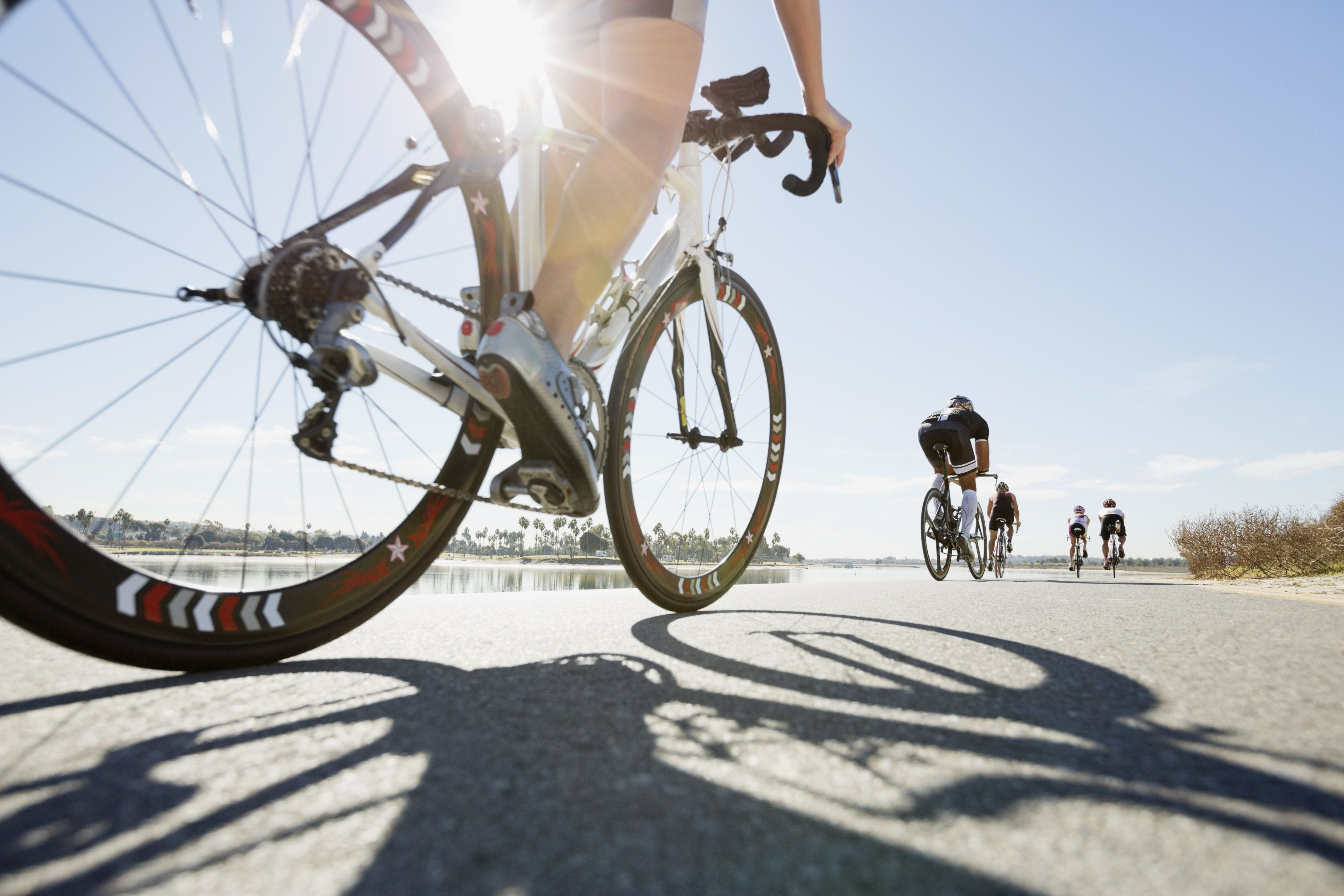 Rear view of triathletes cycling on street