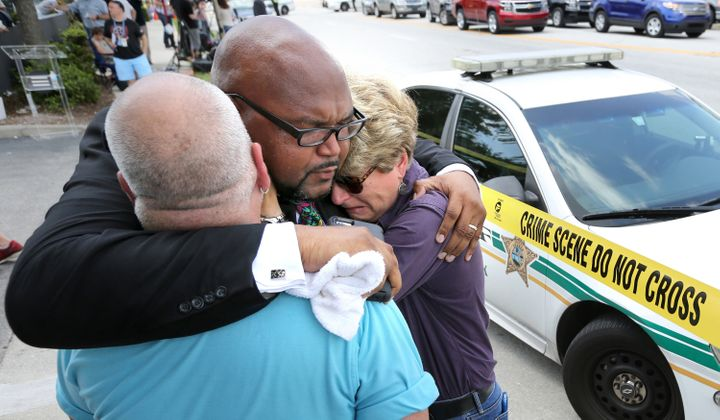 Kelvin Cobaris, a local clergyman, consoles Orlando City Commissioner Patty Sheehan, right, and Terry DeCarlo, an Orlando gay