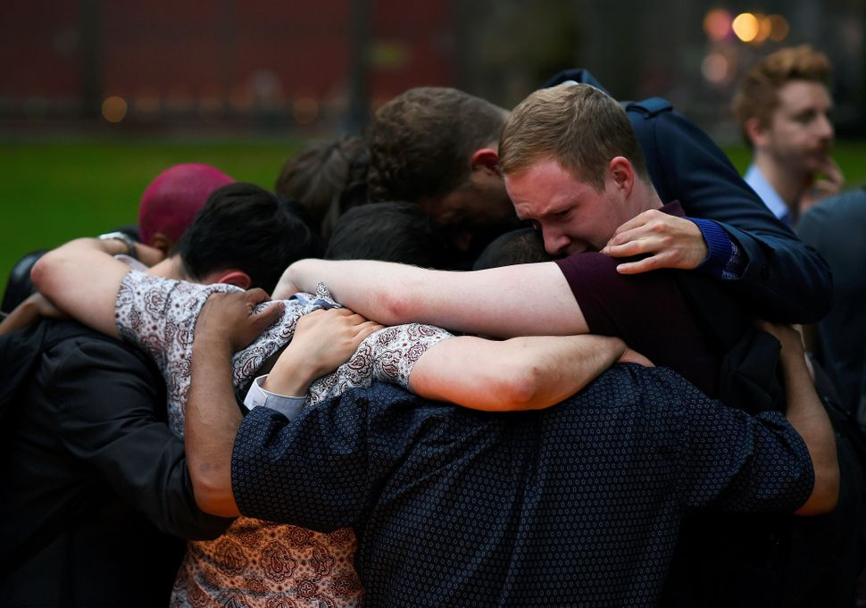 Mourners embrace at St. Anne's Church inSoho.