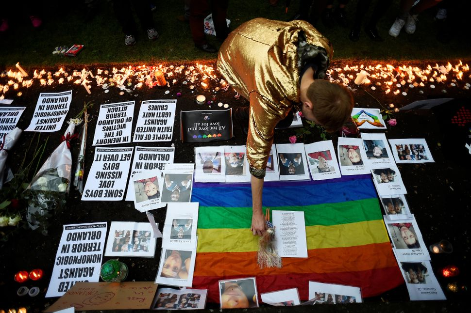 A man places a doll beside candles, flowers and photos of victims of the gay nightclub mass shooting in Orlando, at St Anne's