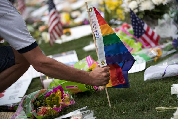 A man plants a Pride flag at a makeshift memorial prior to an evening vigil for the victims of the Pulse Nightclub shoot