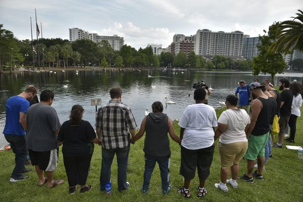 People hold hands during a vigil for the victims of the Pulse nightclub shooting on June 13, 2016 at Lake Eola in Orlando, Fl