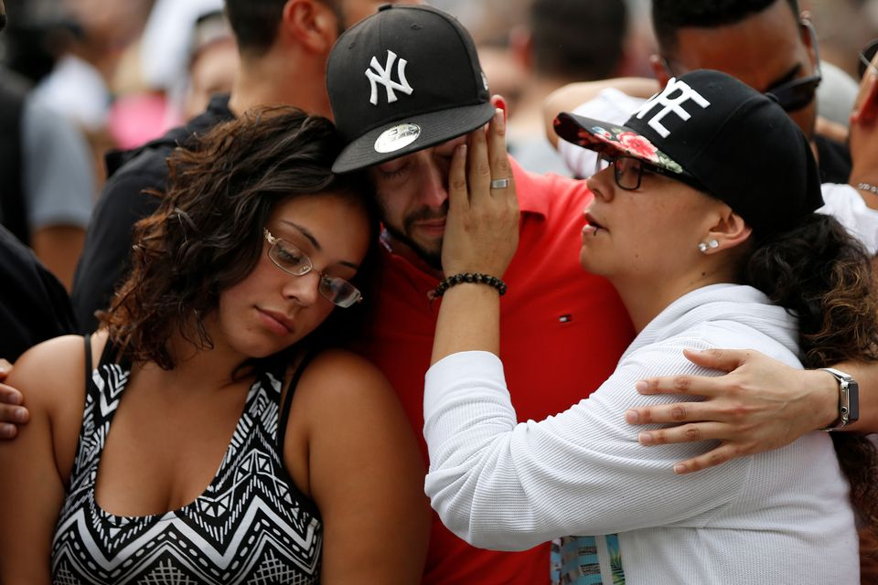 People attend a memorial service Monday, the day after a mass shooting at the Pulse gay nightclub in Orlando, Florida.