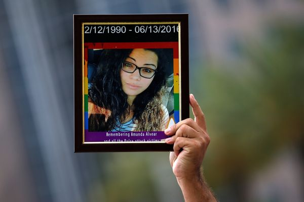 A friend of Amanda Alvear holds up her photo at a memorial service the day after a mass shooting at the Pulse gay nightclub i