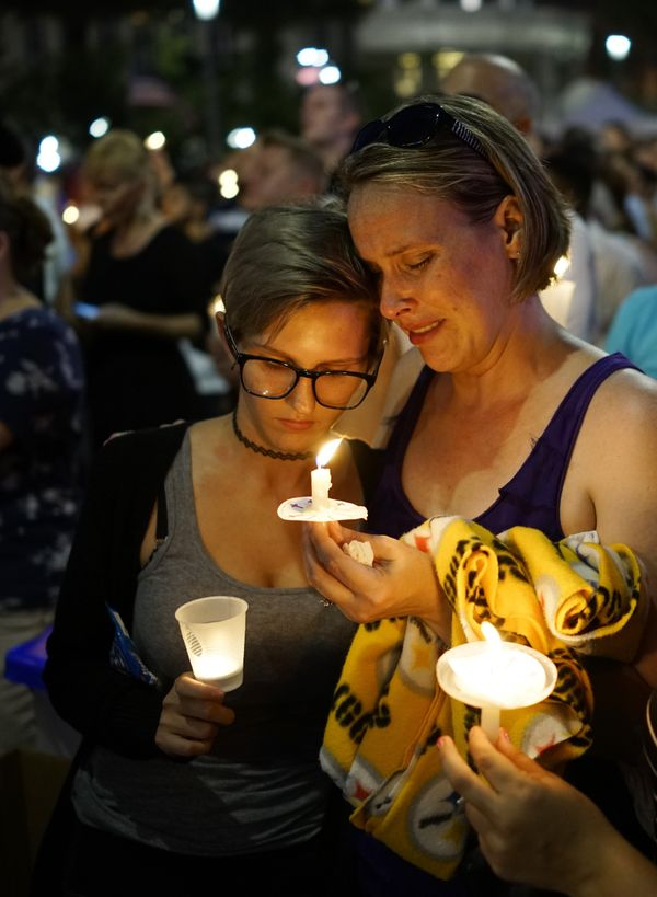 Women hold candles during a vigil for the victims of the Pulse nightclub shooting, on June 13, 2016 at the Dr. Phillips Cente