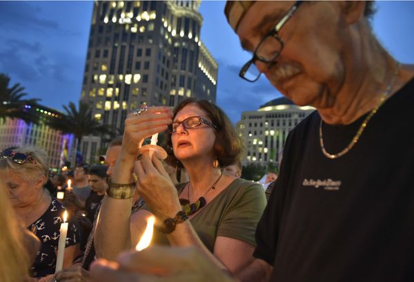 People hold candles during a vigil for the victims of the Pulse nightclub shooting, on June 13, 2016 at the Dr. Phillips Cent