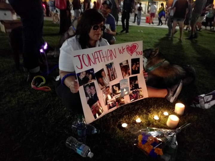 Francesca Garcia sits with a poster adorned with photos of her friend Jonathan Camuy, who died during Sunday's shooting.