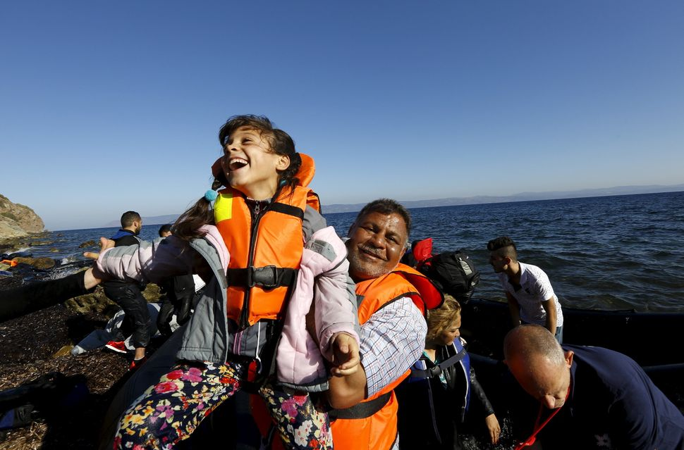 A Syrian refugee girl is lifted by her father soon after arriving on a dinghy at a beach on the Greek island of Lesbos after