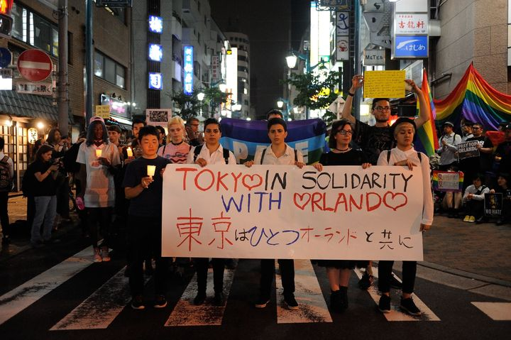 People carrying banners and candles paid tribute to victims of Sunday's mass shooting in a Tokyo, Japan, neighborhood on Tues