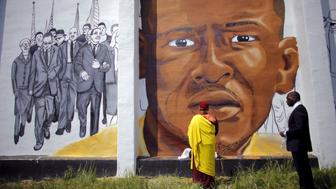 Gyalwang Drukpa (C), a Buddhist leader from South Asia, prays in front of a mural of Freddie Gray in Baltimore, Maryland, May 7, 2015. Gray, 25, sustained spinal injuries after being arrested, and his death on April 19 sparked protests and a day of arson and looting in the largely African American city. REUTERS/Carlos Barria