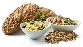 'Healthy eating. A variety of prepared dishes made with whole grains for a healthy lifestyle. Multigrain breads, granola with dried fruit, couscous salad with blueberries, brown rice with bell pepper salad. Shot on white with natural shadow.'