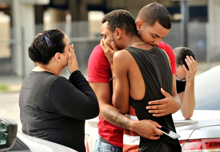 Friends and family members embrace outside the Orlando Police Headquarters in Orlando, Florida, on June 12 after a mass shoot