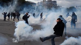 Smoke rises around masked protesters during a demonstration against proposed labour reforms in Paris on June 14, 2016. Twenty-six people were hurt and authorities made 15 arrests as protests in Paris over disputed labour reforms descended into violent clashes between riot police and masked troublemakers. / AFP / DOMINIQUE FAGET        (Photo credit should read DOMINIQUE FAGET/AFP/Getty Images)