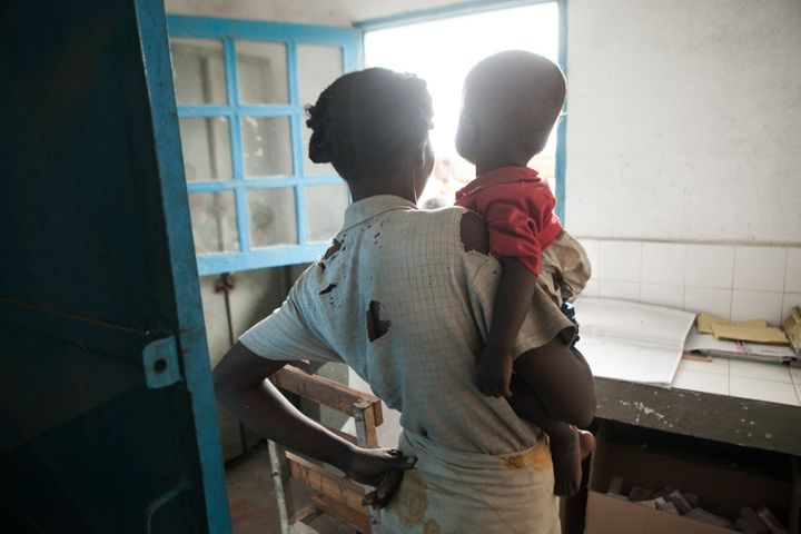This picture taken on March 4, 2015 shows an undernourished 15-month-old baby and his mother waiting for medications in the v