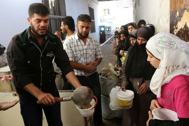 An NGO worker serves food to impoverished Syrian families during the Muslim holy fasting month of Ramadan on June 11, 20