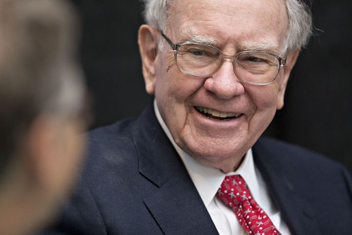 Warren Buffett, chairman and chief executive officer of Berkshire Hathaway Inc., laughs while playing cards on the sidelines