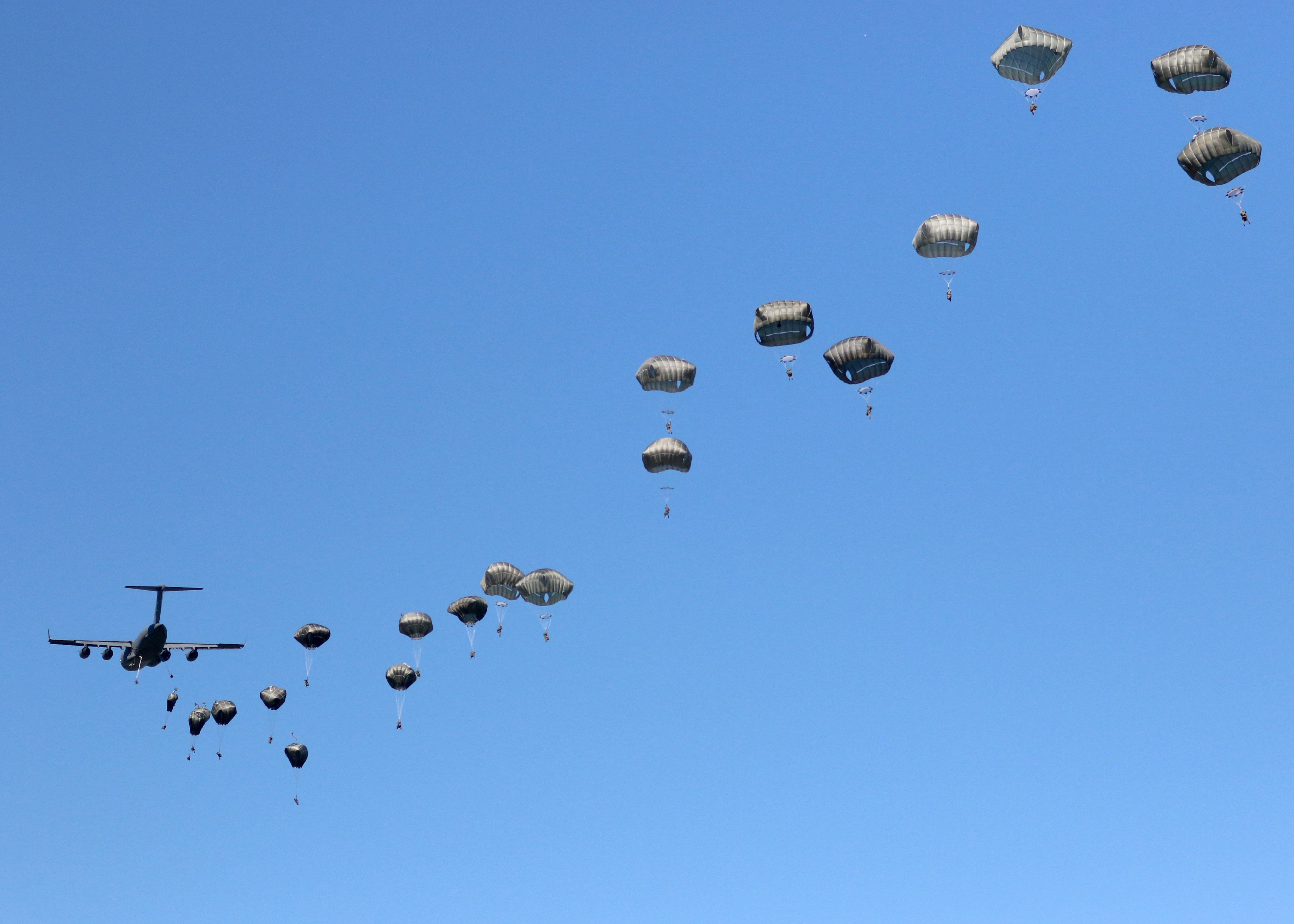 A thousand feet above the ground, a C-17 disgorges its paratroopers in a 22-second pass over thedrop zone.