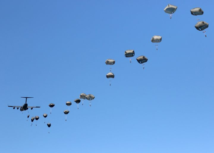 A thousand feet above the ground, a C-17 disgorges its paratroopers in a 22-second pass over the drop zone.