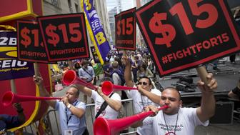 People celebrate the passage of the minimum wage for fast-food workers by the New York State Fast Food Wage Board during a rally in New York July 22, 2015.  New York state moved on Wednesday to raise the minimum wage for fast-food workers to $15 an hour in New York City by the end of 2018 and in the rest of the state by mid-2021. The New York Wage Board, a panel formed by New York governor Cuomo to review the minimum wage for the state's 180,000 fast-food workers, voted unanimously on the pay increase, which would affect some 180,000 workers statewide.  REUTERS/Brendan McDermid