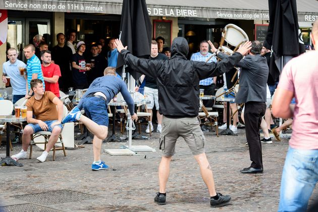 A man throws a chair as a small group of Russian men provoke a group of England supporters in the centre...