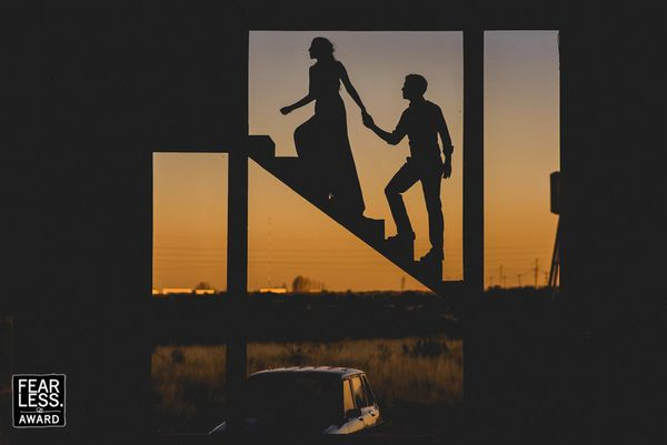 """""""Amidst the rigidly straight lines of this graphic frame, the couple is silhouetted on the one diagonal. As they ascended, ha"""