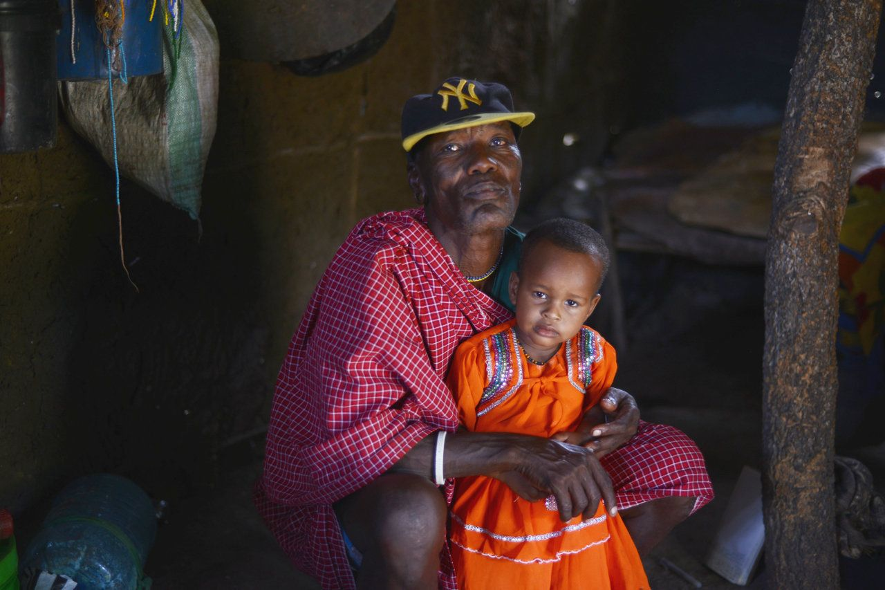 Salumu Kundaya Kidomwita, 60, with the youngest of his 22 children.