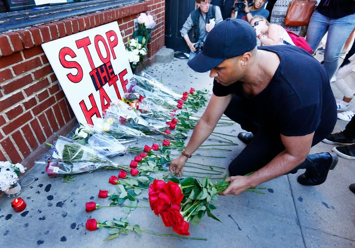 """""""Stop the Hate,"""" reads a sign outside the Stonewall Inn in New York City on Sunday. Nearby, people gathered to honor the vict"""