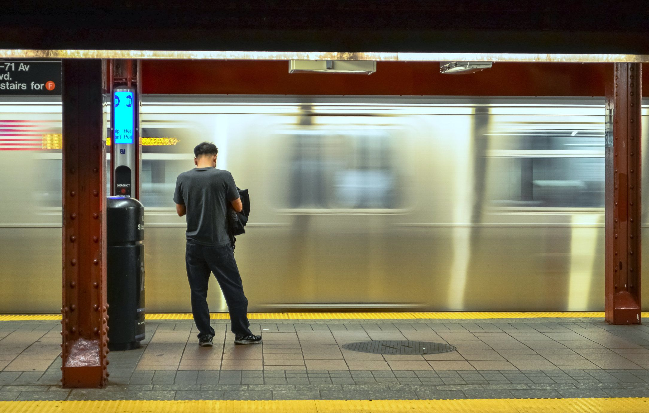 Unrecognizable person waiting as a subway train passes by at high speed creating blurred motion on background in New York City, USA