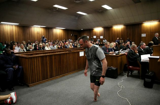 Oscar Pistorius walks across the courtroom without his prosthetic legs during the third day of the resentencing...