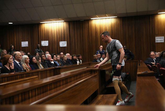 Pistorius prepares to remove his prosthetic legs for the