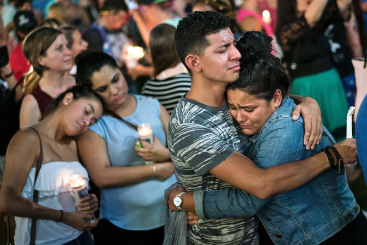 People embrace during a vigil outside the Dr. Phillips Center for the Performing Arts for the mass shooting victims at the Pu