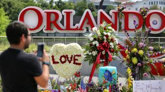 Jose Acevido Negron takes a photo with his iPhone as visitors continue to pay their respects at a makeshift memorial at Orlando Regional Medical Center, a few blocks from Pulse nightclub, on Tuesday, June 14, 2016. (Joe Burbank/Orlando Sentinel/TNS via Getty Images)