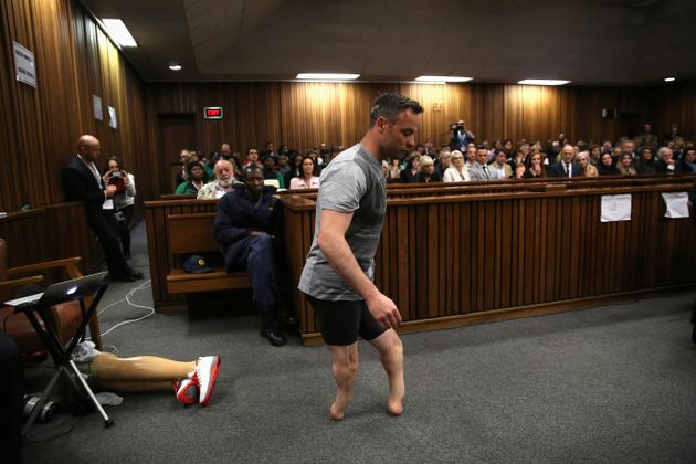 Paralympic gold medalist Oscar Pistorius walks across the courtroom without his prosthetic legs during...