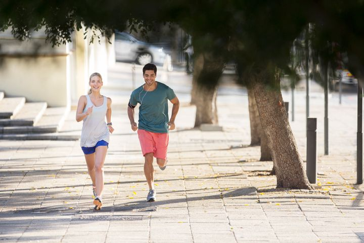 Couple running through city streets together Sam Edwards via Getty Images