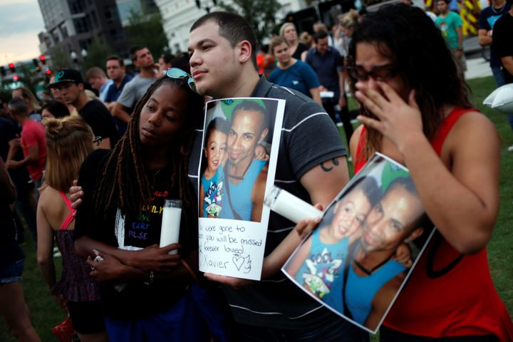Mourners hold a picture of their deceased friend, Xavier Emanuel Serrano Rosado, during a vigil one day after a mass sho