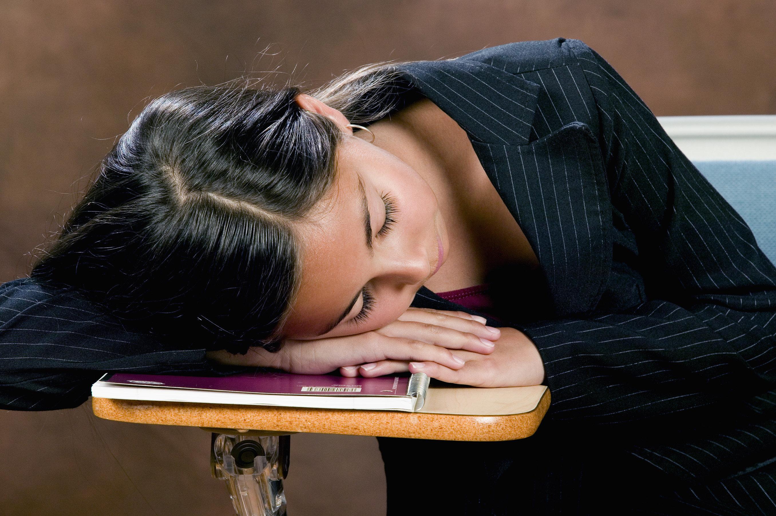 Teenage girl sleeping at desk