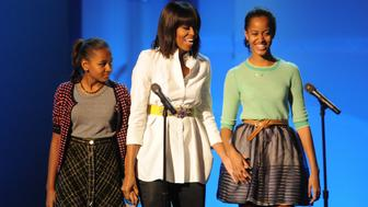 First Lady Michelle Obama flanked by Sasha and Malia attend the Kids Inaugural Concert on January 19 2013 at the Convention Center in Washington, D.C.