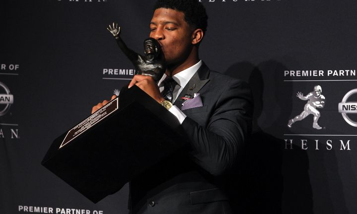 Quarterback Jameis Winston kisses his Heisman Trophy one year after being accused of rape.