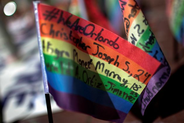 Messages written on rainbow flags are seen placed at a makeshift memorial to remember the victims of...