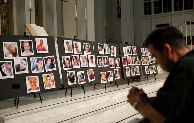 David Olson prays in front of photographs of victims of the shooting at the Pulse gay nightclub, during...