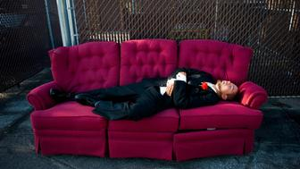 A groomsman takes a nap on a couch before the reception of a wedding in Iowa City, Iowa.
