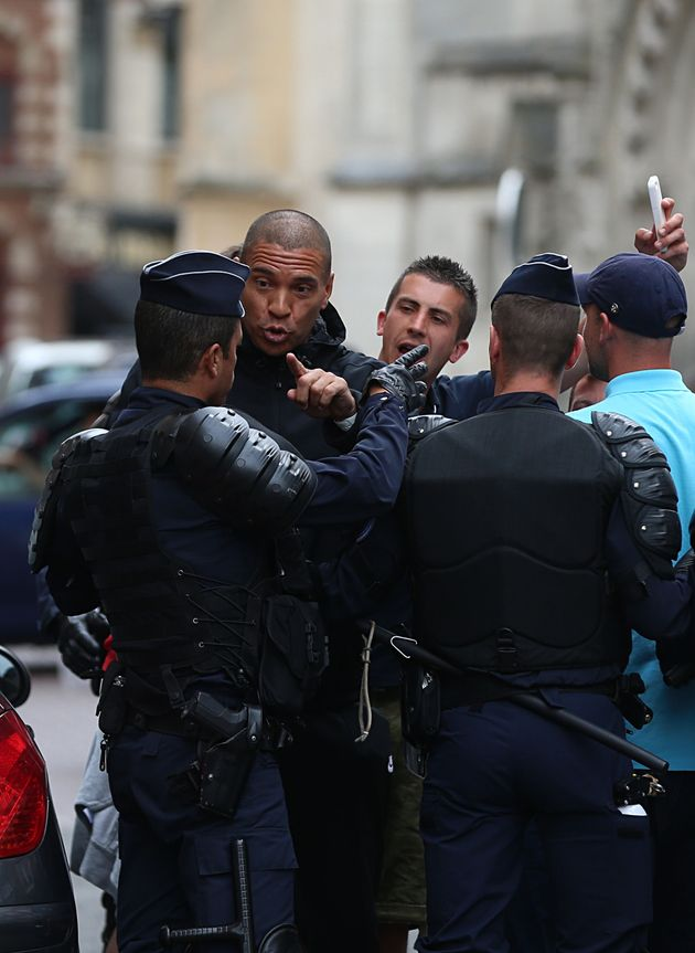 Former footballer Stan Collymore chats to police outside the train station in Lille city
