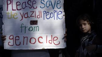 A migrant child stands next to a placard reading 'Please save the Yazidi people from genocide' at the Moria detention center during a visit of Pope Francis in Mytilene, on the Greek island of Lesbos, on April 16, 2016. 'We are all migrants,' Pope Francis said on April 16 on a visit to the Greek island of Lesbos to give hope to thousands facing deportation after risking their lives to reach Europe. The pontiff's visit came amid continuing criticism of a deal reached last month to end Europe's refugee crisis by sending all irregular migrants who land in Greece back to Turkey. / AFP / ARIS MESSINIS        (Photo credit should read ARIS MESSINIS/AFP/Getty Images)