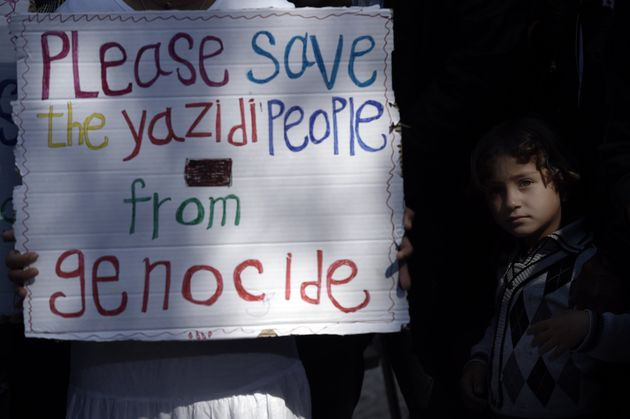 A migrant child stands next to a placard reading 'Please save the Yazidi people from genocide' at the...