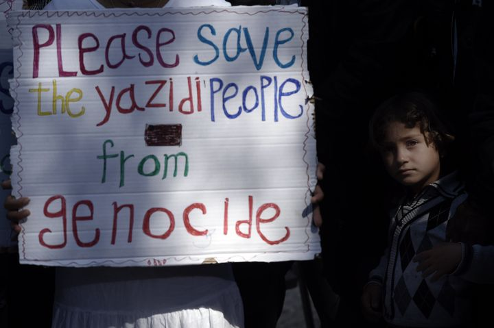 A migrant child stands next to a placard reading 'Please save the Yazidi people from genocide' at the Moria detention center