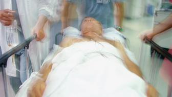 Emergency room doctors pushing patient on gurney (blurred motion)