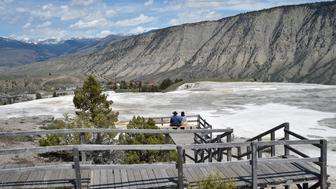 Tourists enjoy the view of the Mammoth Hot Springs at Yellowstone National Park on May 12, 2016. Yellowstone, the first National Park in the US and widely held to be the first national park in the world, is known for its wildlife and its many geothermal features.  / AFP / MLADEN ANTONOV        (Photo credit should read MLADEN ANTONOV/AFP/Getty Images)