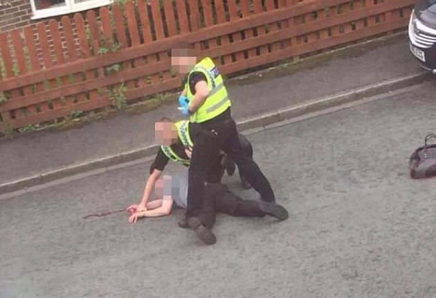 A man being pinned to the ground by police near the scene of the